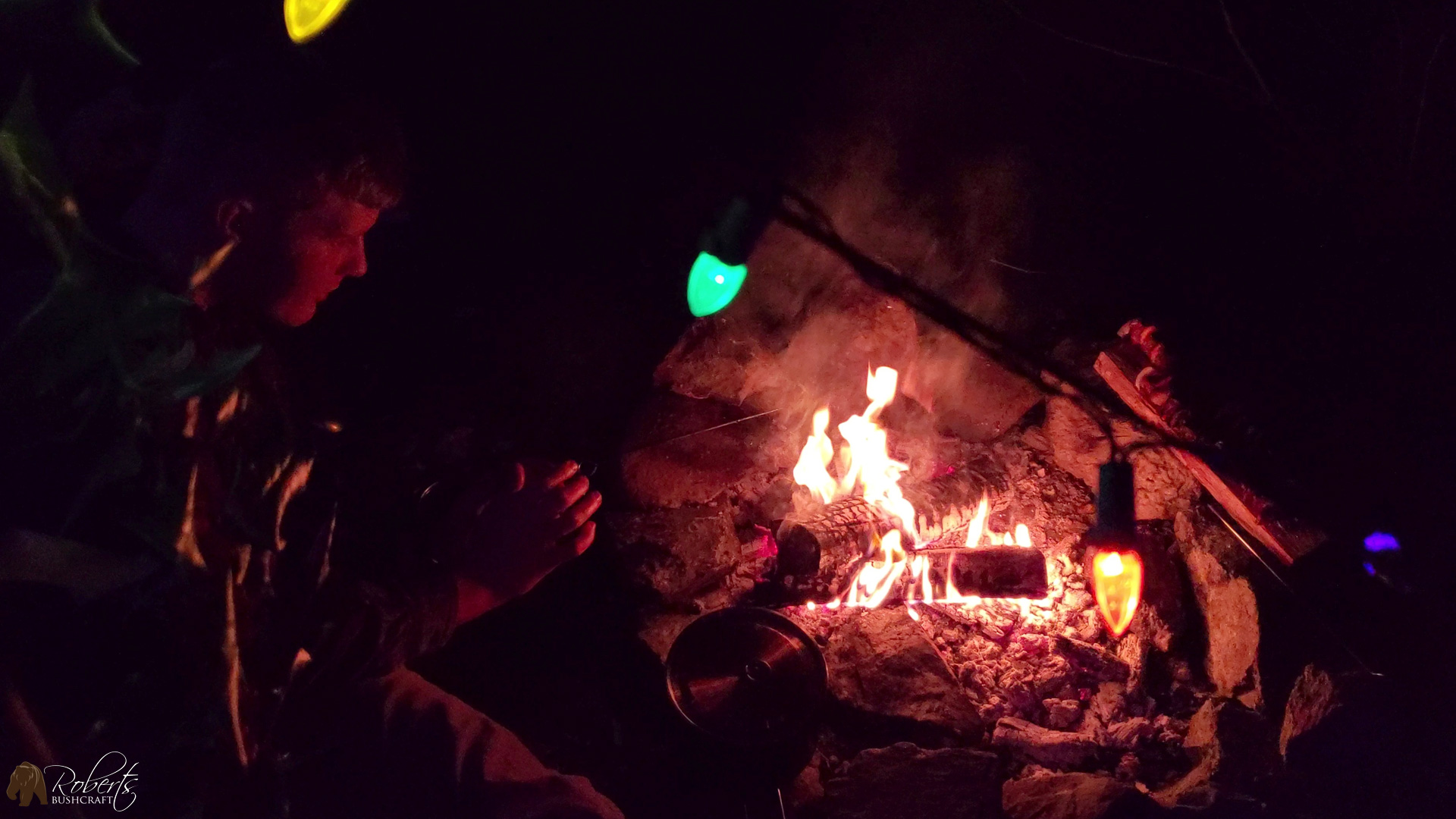 Christmas lights on an Aqua Quest tarp highlight warming my hands over the campfire on the Roanoke River